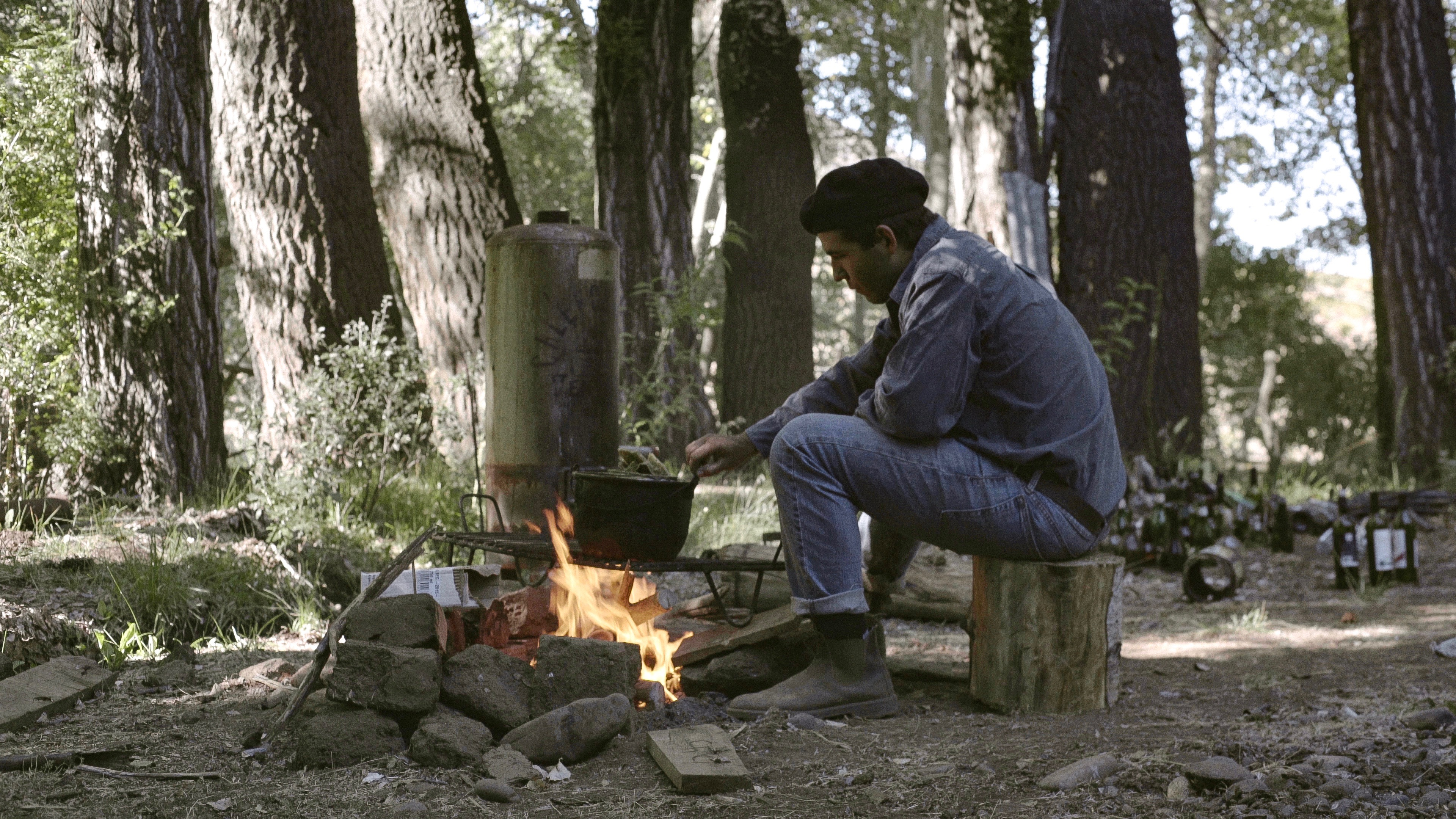 Intern cooking over a fire at Estancia Ranquilco in Patagonia Argentina