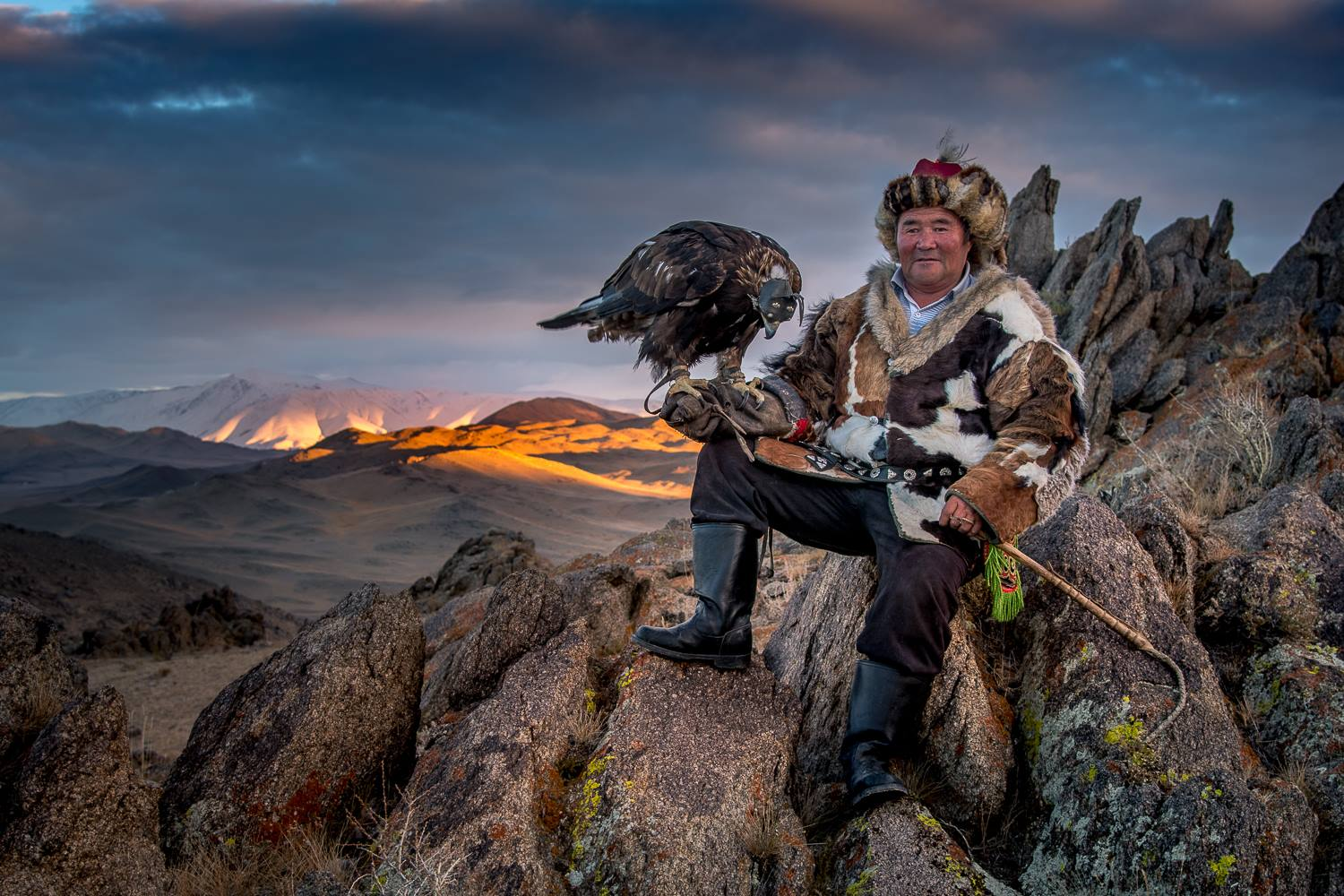 Kazakh eagle hunter and eagle sitting in the mountains