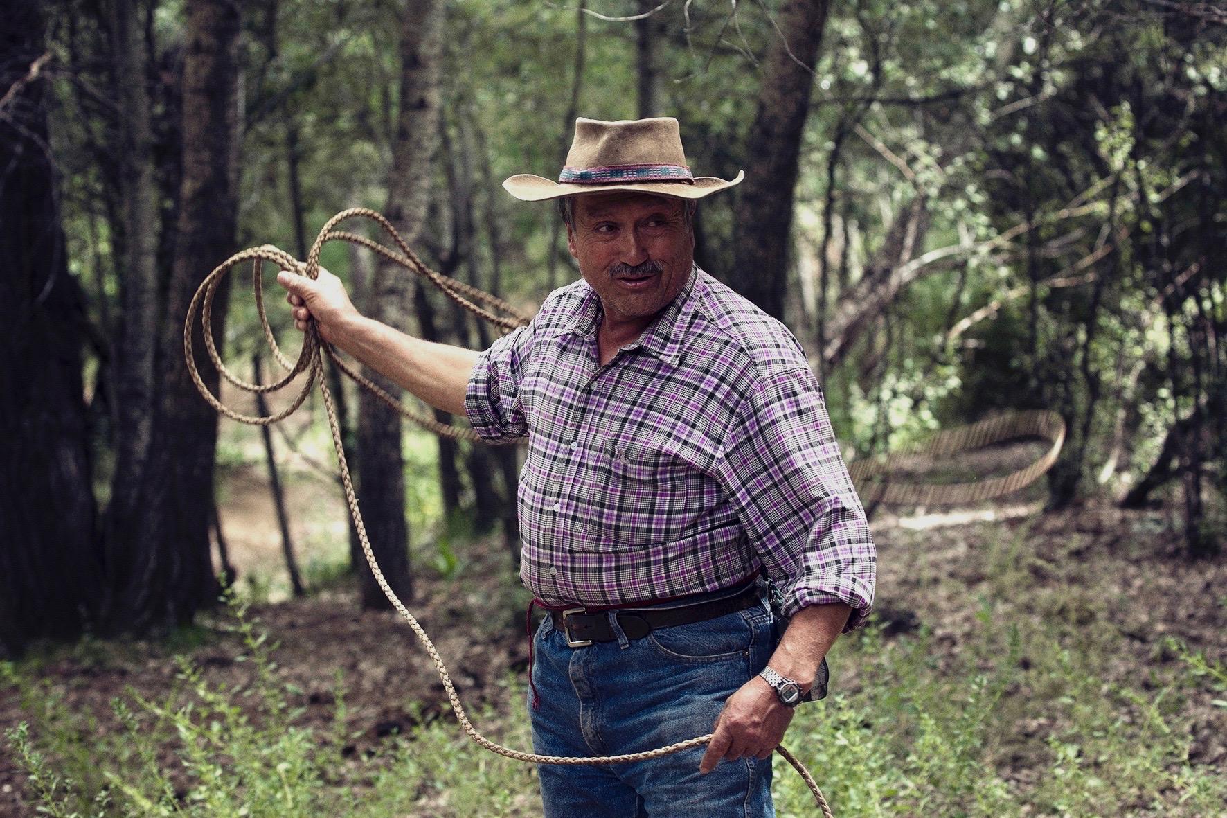 Gaucho throwing lasso in corral at Estancia Ranquilco ranch in Patagonia Argentina