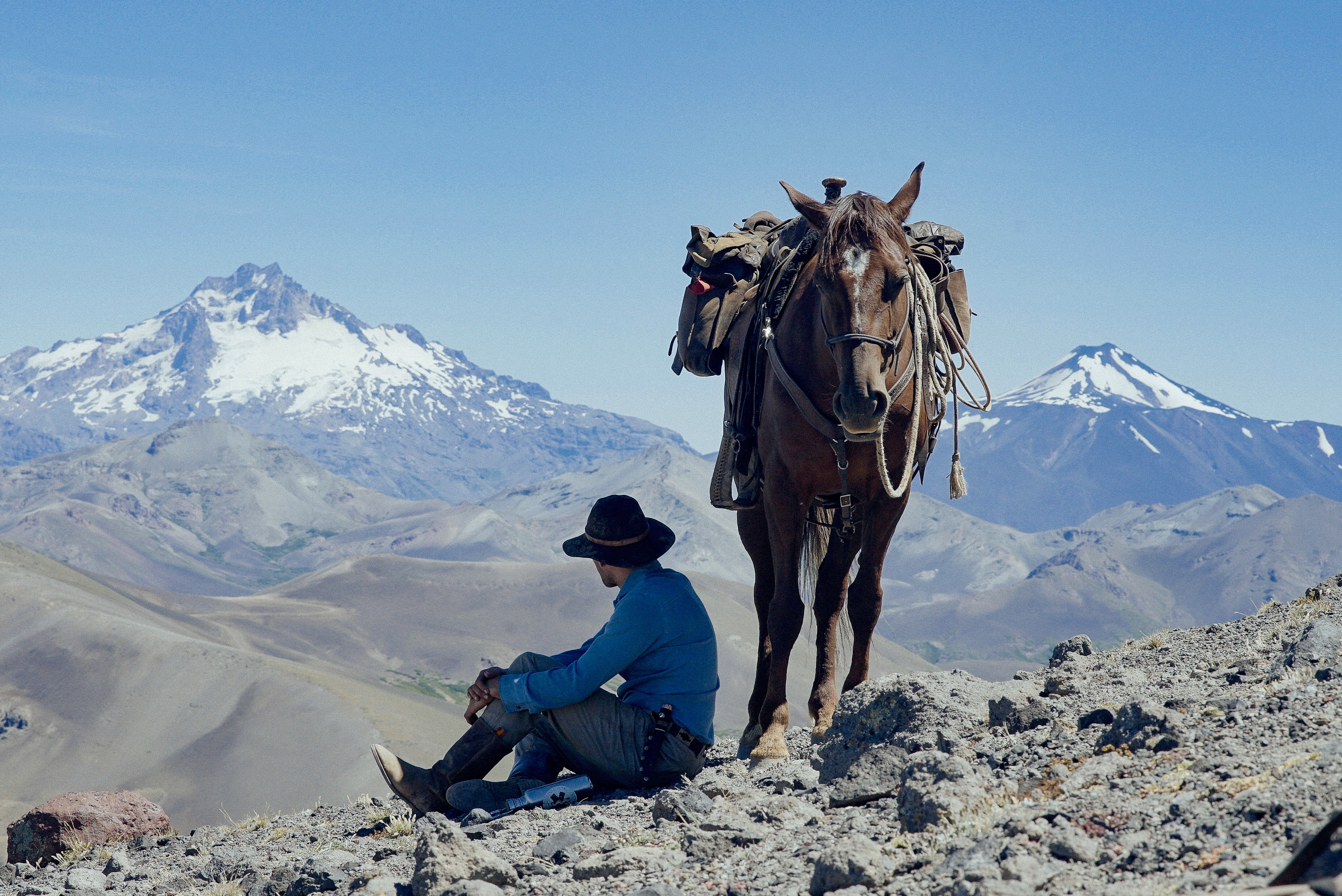 Man sitting next to horse overlooking snow capped mountains in Patagonia