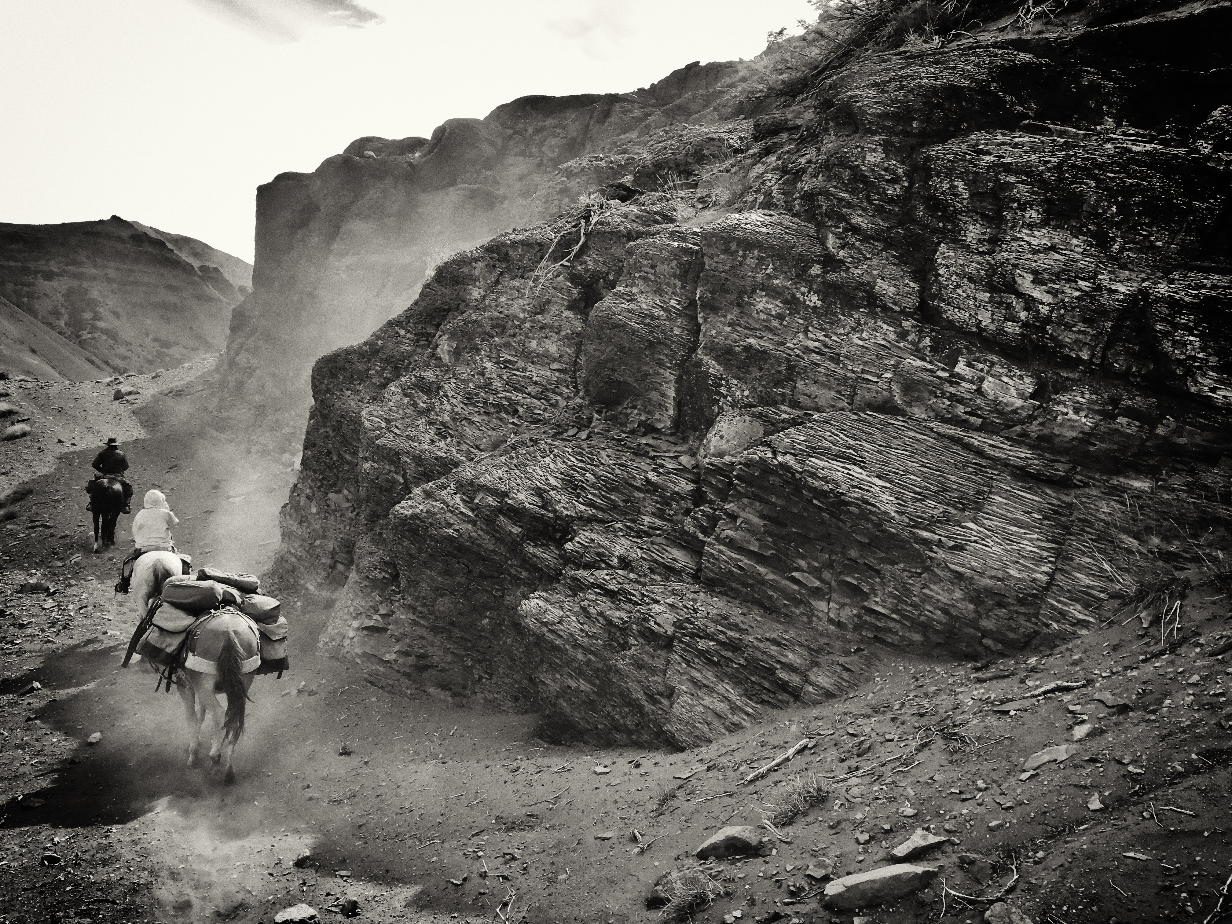 Black and white photo of riders and pack mule heading into the Patagonian mountains