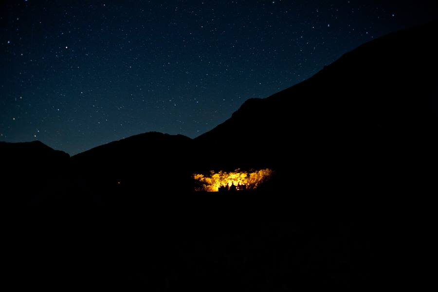 Silhouette of mountains against starry night sky with campers and bonfire