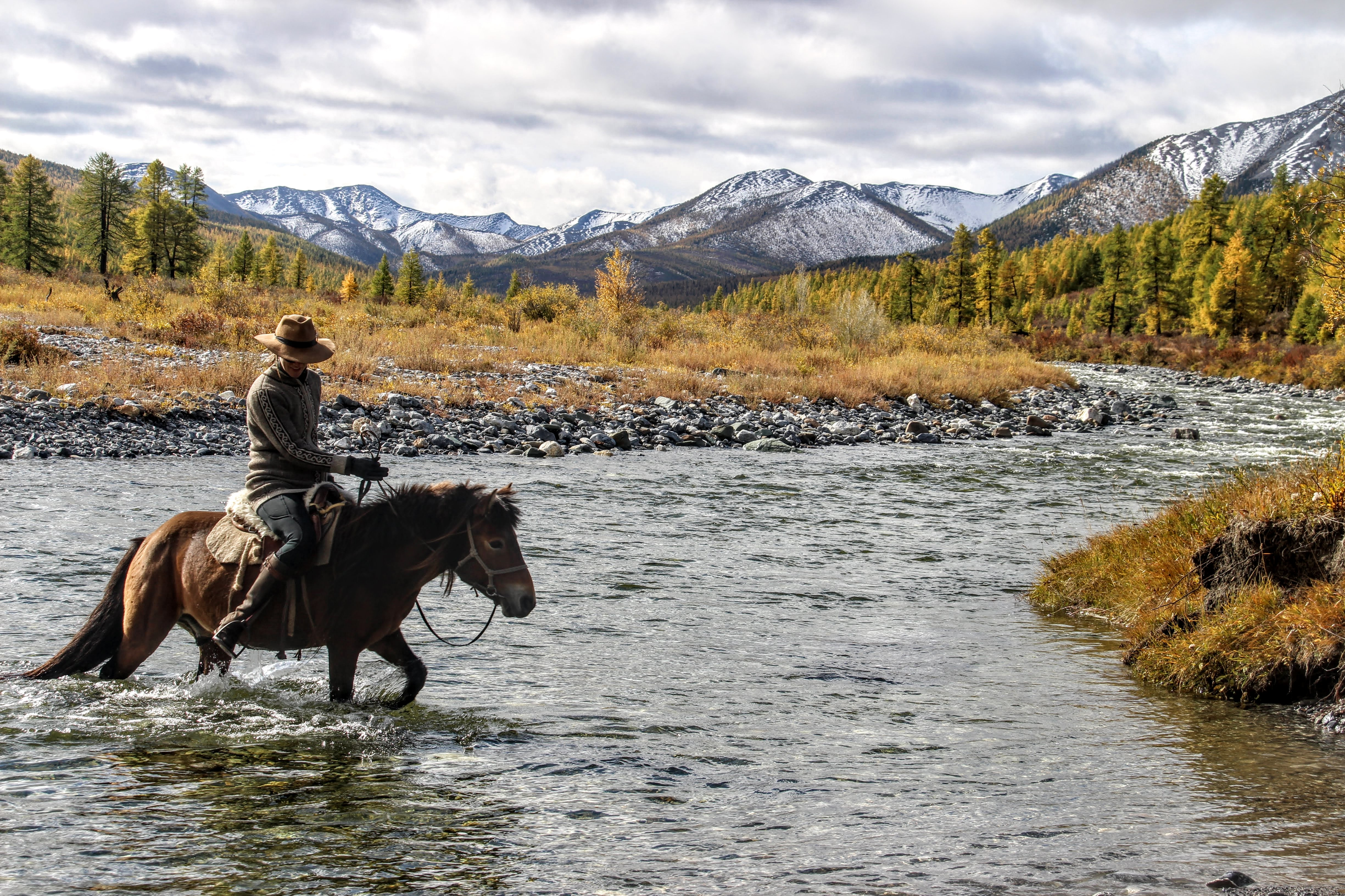 Rider and horse crossing river in Northern Mongolia with snowy mountains in background