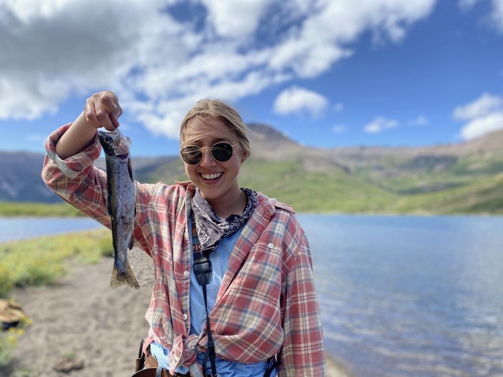 Annie Lord, 2020 intern, holding up her fish at Laguna Negra, Estancia Ranquilco's horse pack trip destination