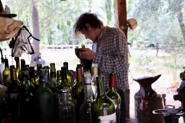 Man cleaning empty Argentine Malbec bottles to reuse and make into glasses