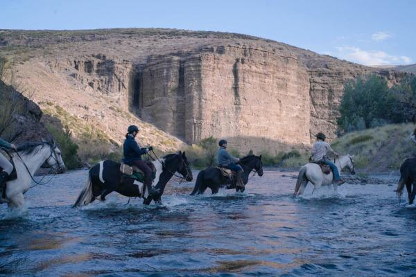 Riders on horseback crossing the river on the approach to Estancia Ranquilco in Patagonia Argentina