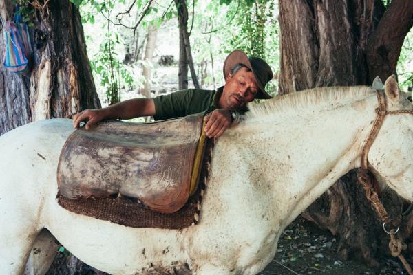 Argentina gaucho saddling his horse at the estancia