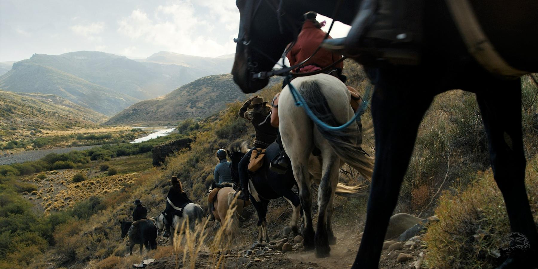 String of riders descending into a river valley in the backcountry of Estancia Ranquilco