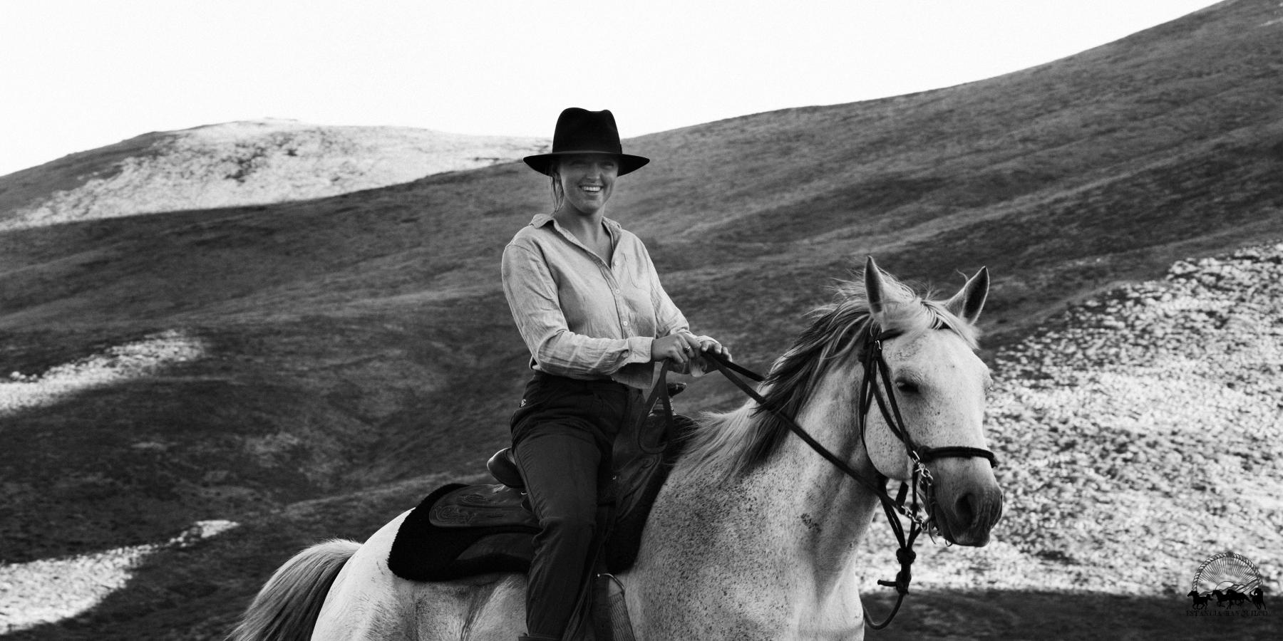 Black and white photo of woman riding criollo horse at Estancia Ranquilco in Patagonia Argentina