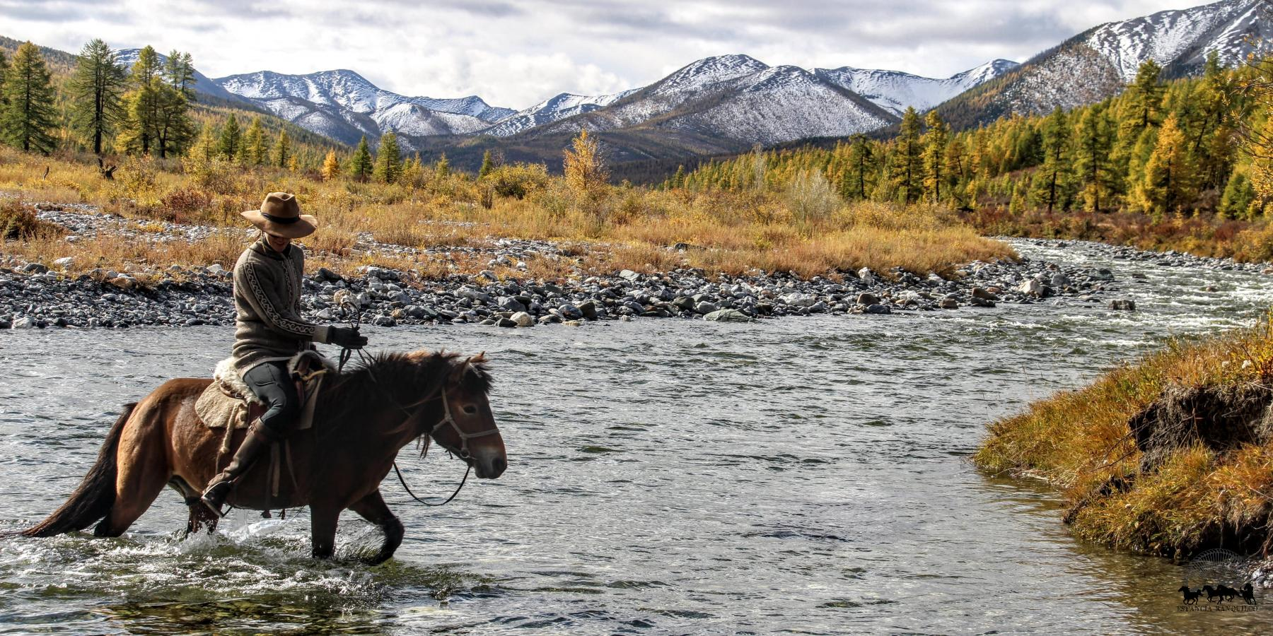 Woman crossing river on horseback in Mongolia with Estancia Ranquilco