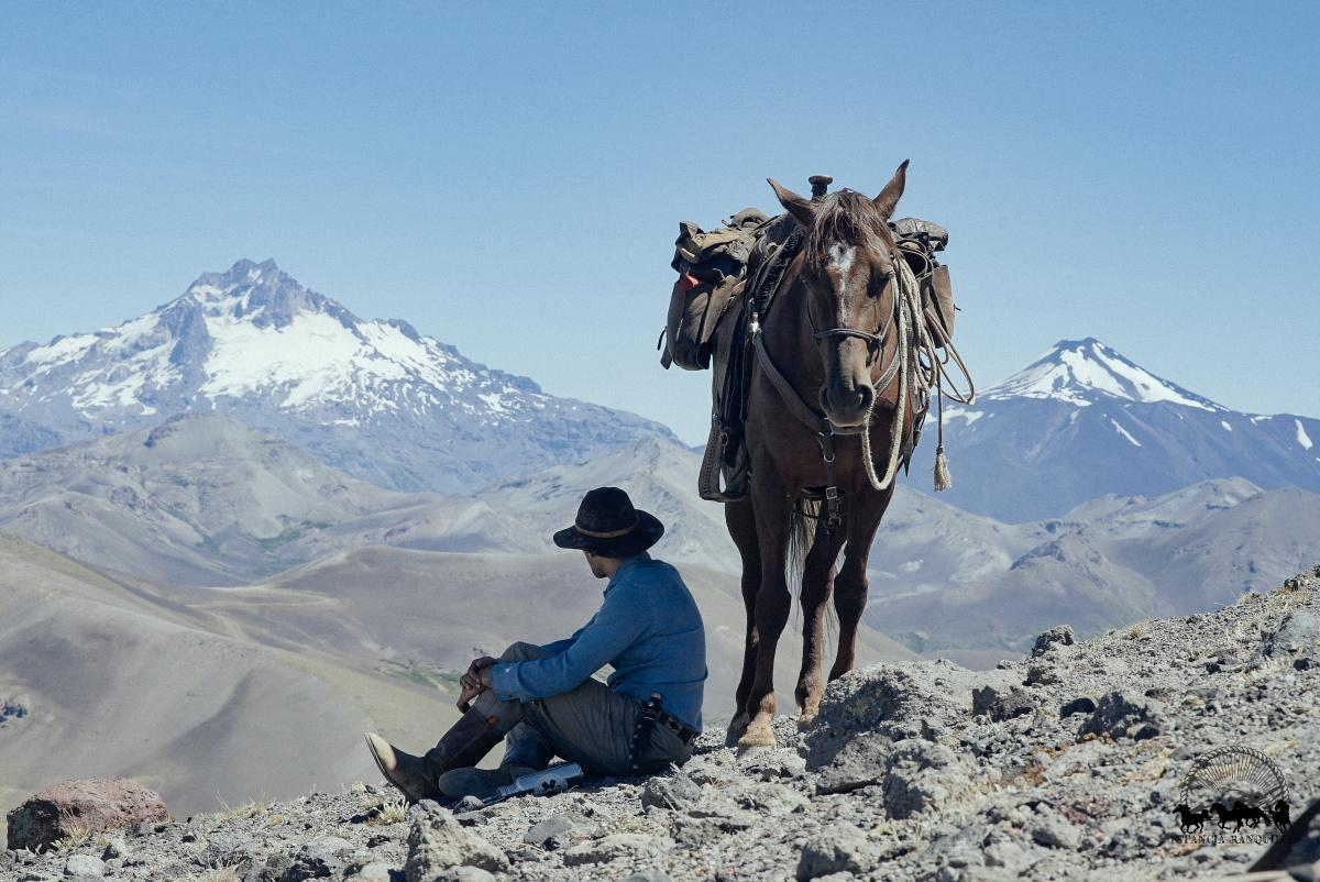 Man and horse overlooking snow capped peaks on mountain pass at Estancia Ranquilco in Patagonia Argentina