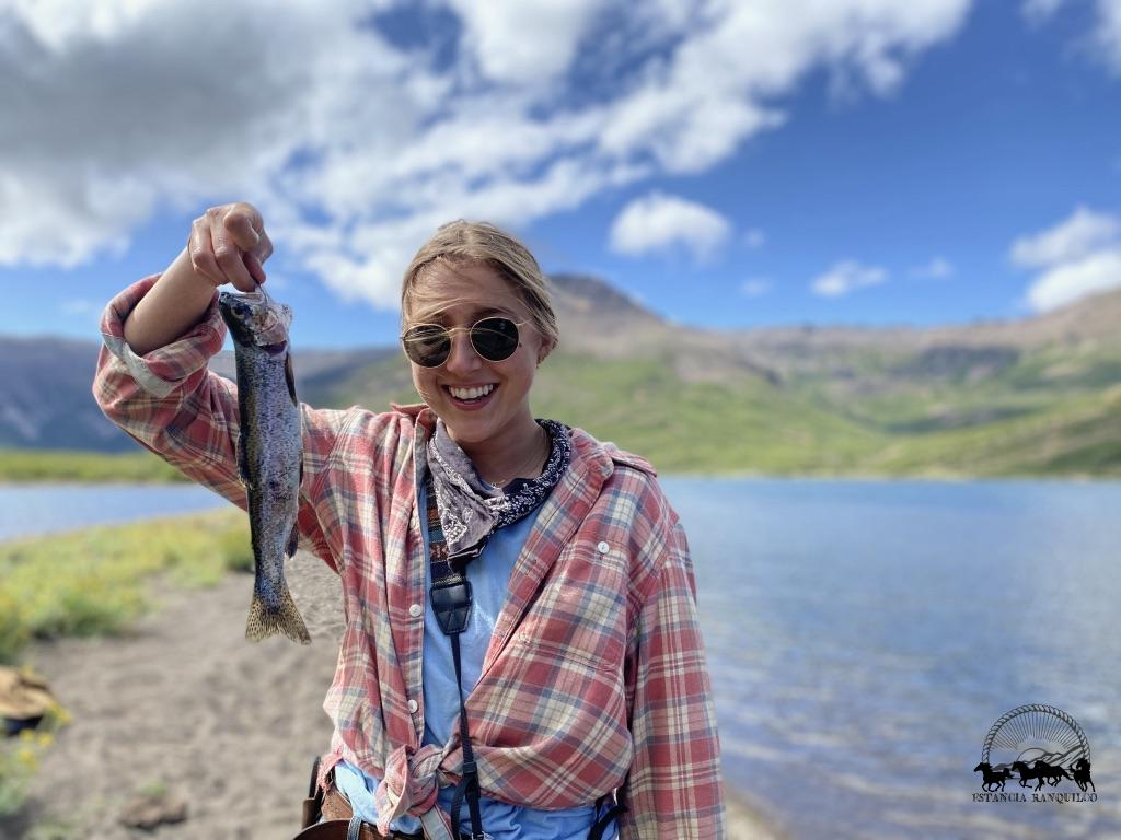 Annie Lord, 2020 intern, holding up her fish at Laguna Negra, Estancia Ranquilco's horse pack trip destination