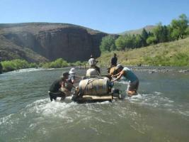 Group of people transporting a wine barrel across the river at Estancia Ranquilco