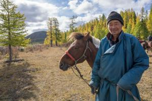 Nomadic Mongolian herdsman posing with his horse during an Estancia Ranquilco horse pack trip.