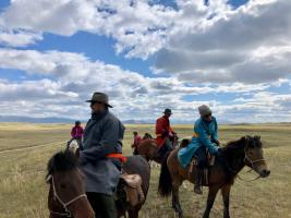 Guests laughing while mounted on their Mongolian horses in the Darkhad Valley during an Estancia Ranquilco horse pack trip in Northern Mongolia