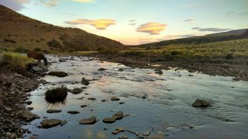 Evening light casting shadows on the Estancia Ranquilco river in the Andes