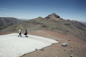 Two people playing in the snow on top of a mountain pass on horse trek at Estancia Ranquilco in Patagonia Argentina