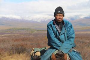 Nomadic herdsman riding his horse in Mongolia with snow capped mountains in the background