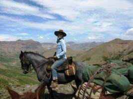 Woman sitting on criollo horse on top of a mountain at Estancia Ranquilco in Patagonia Argentina