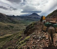 Riders and horses climbing a mountain with dramatic sky in background on Estancia Ranquilco horsepack trip