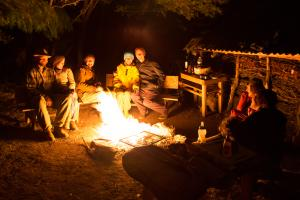 Friends sitting around a fire at night in the mountains of Patagonia