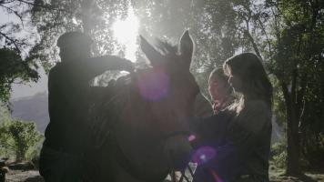 Three people packing a mule in preparation for a horse pack trip at Estancia Ranquilco in Patagonia Argentina