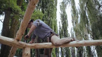 A man saws a beam at horse ranch Estancia Ranquilco in Patagonia Argentina
