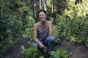 Lulu the gardener in an arch of peas in the garden