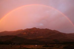 Photo of rainbow over the Patagonia mountains at dusk on a pack trip