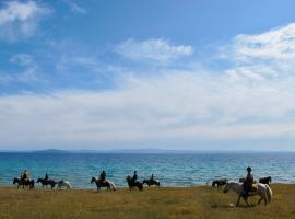 People riding horses along the shore of Lake Khovsgol on a horse trek through Mongolia with Estancia Ranquilco
