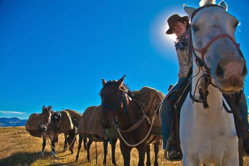 Woman riding horse leading loaded pack mules through Estancia Ranquilco in Patagonia Argentina